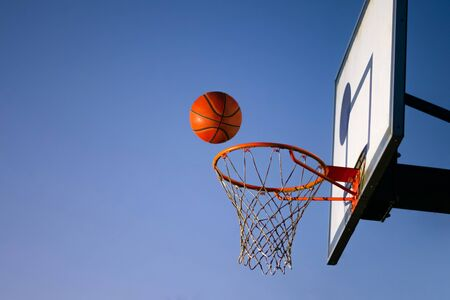 Street basketball ball falling into the hoop. Close up of orange ball above the hoop net with blue sky in the background. Concept of success, scoring points and winning. Copy space