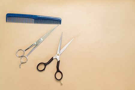 Professional hairdresser tools on brown background. Classic barber equipment: comb and scissors