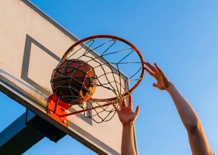 Street basketball slam dunk competition. Close up of ball falling into the hoop. Urban youth game. Concept of success, scoring points and winning Banco de Imagens