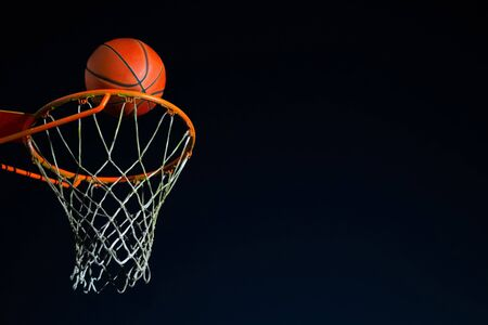 Street basketball ball falling into the hoop at night. Urban youth game. Close up of orange ball above the hoop net. Concept of success, scoring points and winning Banco de Imagens