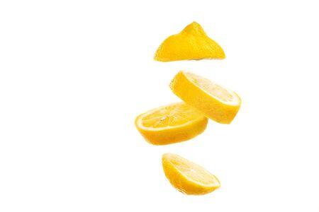 Sliced lemon floating on white background. Fruit slice falling on bright backdrop.