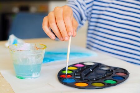 Little kid painting with watercolor paint at home school. Close up of hand dipping brush into colourful paint. Creativity and stay at home concept