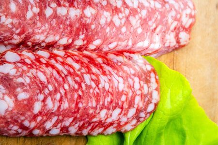 Close up of round salami slices with white fat next to green salad on wooden cutting board. Thin slices of delicious salami meat