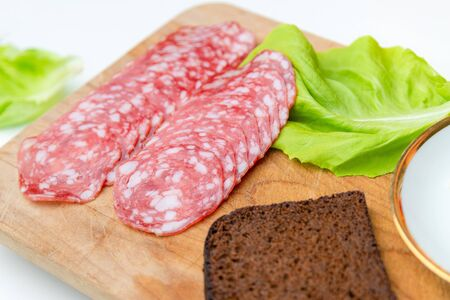 Sandwich ingredients: dark bread, salami, lettuce and butter on wooden cutting board. Top view of classic breakfast at home