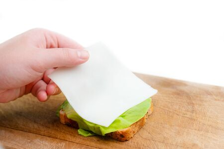 Close up of hand placing cheese on bread slice with salad leaf on wooden cutting board. Making sandwich