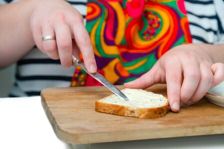 Close up of hand with a kitchen knife spreading butter on the bread slice on wooden cutting board. Making sandwich for breakfast