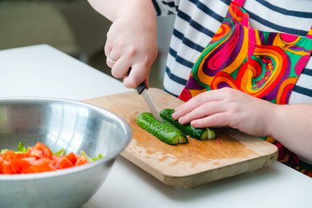 Woman making salad at home - cutting cucumber with a knife on wooden board in the kitchen. Close up of hands with a knife slicing cucumber