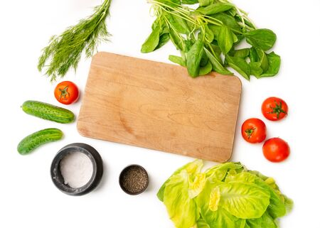 Various vegetables laying on the table in the kitchen next to the cutting board. Top view of the salad ingredient: tomatoes, cucumber, salad leaf, spinach, dill and seasoning.