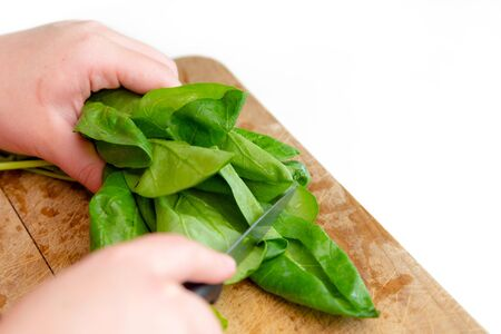 Close up view of chef hands cutting green spinach on wooden cutting board. Making healthy salad at home