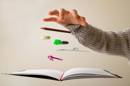 Levitating school supplies for math - notebook, pen, ruler, pencil, divider and eraser levitating between student hands. Concept of education and creativity