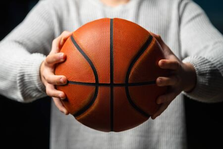 Close up of professional basketball player holding a ball in the hand. Street basketball athlete preparing for competition. Concept of success, scoring points and winning Reklamní fotografie