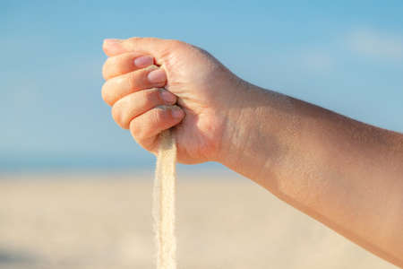 Close up of sand pouring from the hand on the beach on a sunny summer day. Playing with sand on vacation.