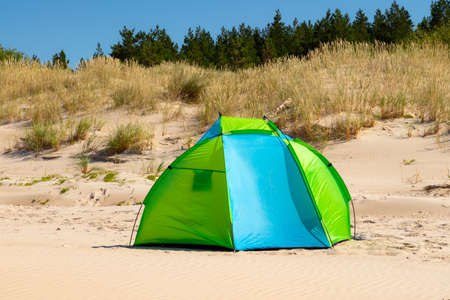 Wind breaker tent on a sandy beach by the sea. Nobody. Colorful tent protection from wind and sunburn. 스톡 콘텐츠