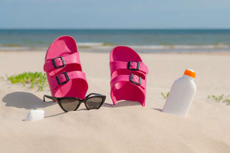 Pink sandals, sunglasses and sunscreen at the beach on a beautiful sunny day. Slippers in the sand by the sea. Flip flops at the shore by the ocean. 스톡 콘텐츠