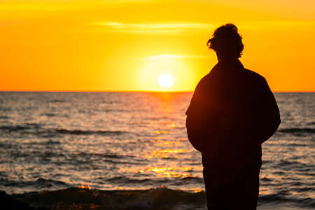 Dark silhouette of a man standing by the sea at golden sunset. Lonely teenager looking a setting sun.