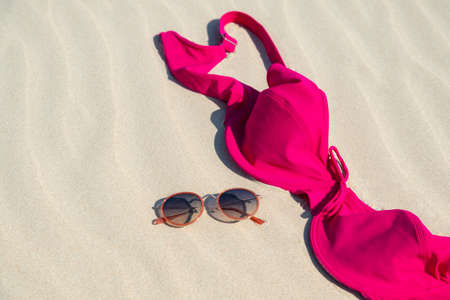 Close up of woman bra and glasses on the sand. Concept of sunbathing naked on the nude beach. Naturalist lifestyle. Nobody. 스톡 콘텐츠
