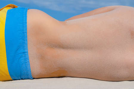 Sandy male back laying on the beach on a sunny day. Sandy curve of the athletic mans hips. Holiday blue sky background.