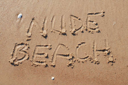 Nude beach letters written on the sand at the beach on a sunny day. Naked sunbathing. Naturalist lifestyle.