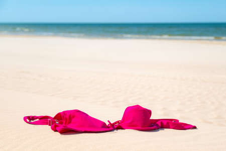 Close up of woman bra at nude beach. Concept of sunbathing naked on the sandy ocean beach. Naturalist lifestyle. Nobody.