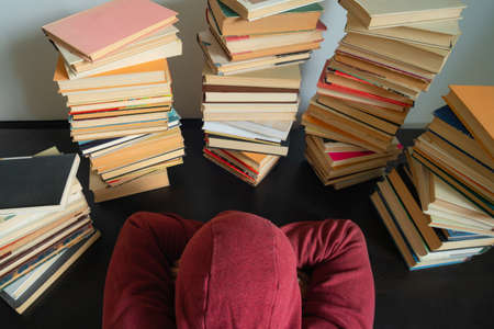 Student wearing a hoody sleeping next to big stack of books on the table. Studying before the exam. Concept of education and studying