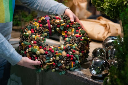 Person holding beautiful and colourful hand made Christmas wreath, green spruce branches decorated with pine cones and other decorations. Christmas chaplet in hands. 스톡 콘텐츠