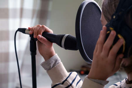 Closeup of teenager recording music in home studio. Girl with headphones and microphone recording song