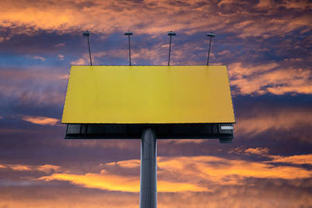 Blank billboard with copy space surrounded by colorful sunset sky. Large empty template, advertising space