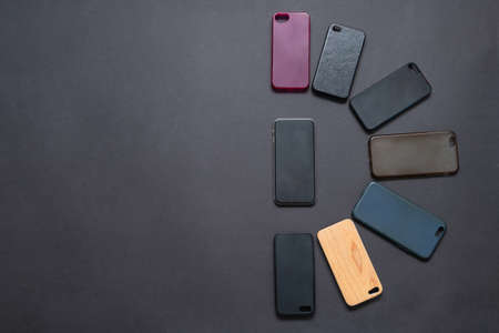 Pile of multicolored plastic back covers for mobile phone on black background. Choice of smart phone protector accessories. A lot of silicone phone backs or skins next to smart phone 스톡 콘텐츠