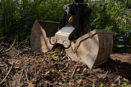 Heavy industrial machine scoop wooden branches and dirt of the ground. Hydraulic shovel lifting wood and waste from the garden 스톡 콘텐츠