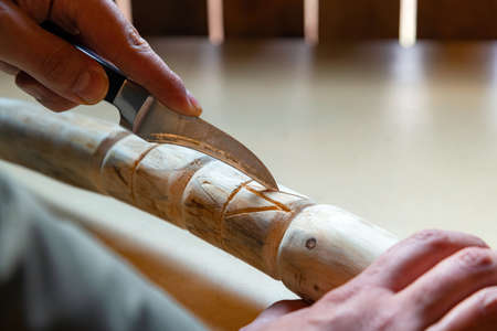 Process of man making wooden walking stick indoors during quarantine. Carving wood stick on the table using knife