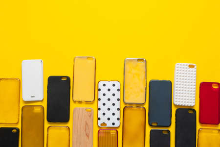 Pile of multicolored plastic back covers for mobile phone. Choice of smart phone protector case accessories background. Silicone phone backs on yellow background