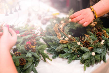 Christmas wreath weaving workshop. Woman hands decorating holiday wreath made of spruce branches, cones and various organic decorations on the table 스톡 콘텐츠