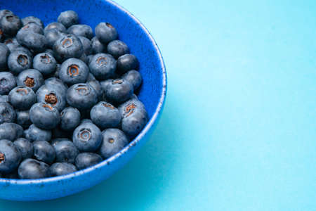 Closeup of ceramic bowl full of blueberries on blue background. Ripe blueberry plate. Organic and healthy food.