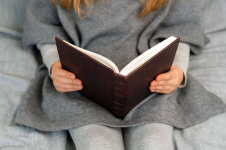 Caucasian girl with blond hair reading a book. Young teenager learning at home school in quarantine.