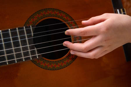 Close up of hand playing acoustic guitar. Practicing classic musical instrument. Home school education 스톡 콘텐츠