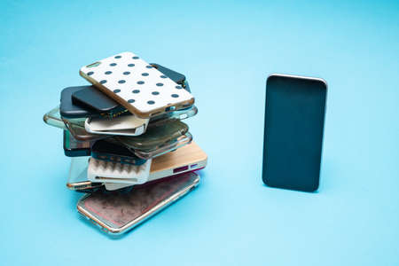 Pile of multicolored plastic back covers for mobile phone on blue background. Choice of smart phone protector accessories. A lot of silicone phone backs or skins next to smart phone