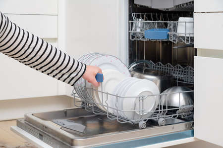 Close up of hand unloading dish washer in the kitchen. Person taking of appliances of full shelf of dishwasher. 免版税图像