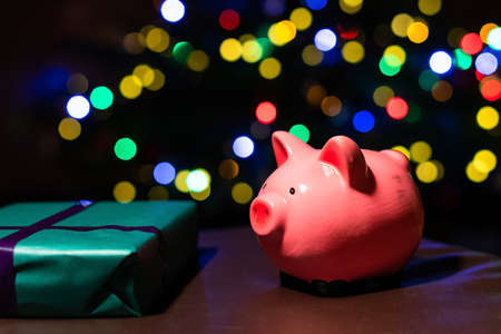 Saving money for Christmas present. Holiday piggy bank with colourful bokeh balls in the background.