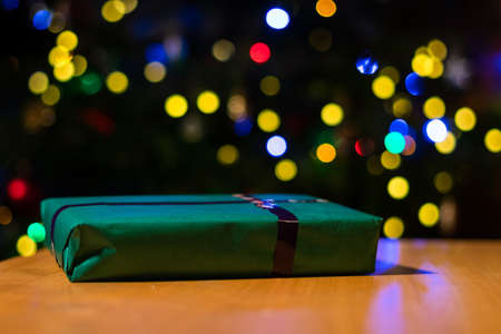 Close up of Christmas presents with colourful bokeh balls in the background. Wrapped gift on holiday table