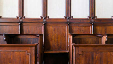 Detail of traditional hard wood courthouse, church choir sitting area. Interior with empty wooden seats
