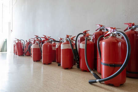 Bunch of expired fire extinguishers on the floor next to the wall. Renewal of extinguishers for businesses.