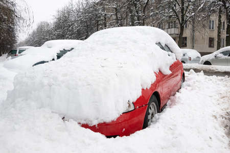 Car under thick blanket of snow after storm. Vehicles buried under ice. Nobody