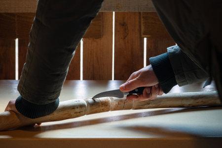 Process of man making wooden walking stick indoors during quarantine. Banco de Imagens