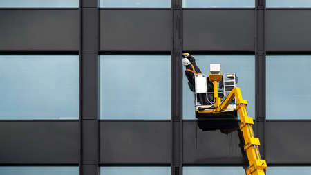 Male cleaner cleaning glass windows on modern buildings high in the air on a lift platform.