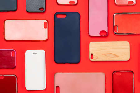 Pile of multicolored plastic back covers for mobile phone. Choice of smart phone protector accessories on red background. A lot of silicone phone backs or skins next to each other