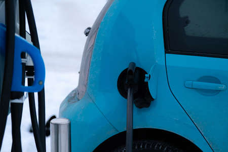 Charger plug inserted in electric car on snowy winter background. Green energy.