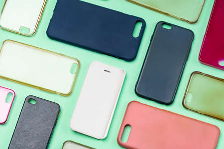 Pile of multicolored plastic back covers for mobile phone. Choice of smart phone protector accessories on green background. A lot of silicone phone backs or skins next to each other