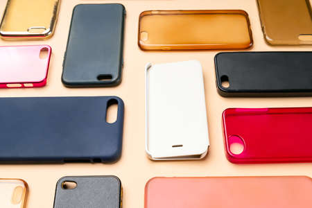 Pile of multicolored plastic back covers for mobile phone. Choice of smart phone protector accessories on neutral background. A lot of silicone phone backs or skins next to each other