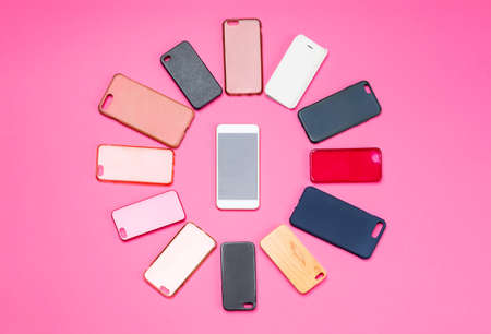 Choice of multicolored plastic back covers for mobile phones on pink background with a smart phone on the side Banco de Imagens