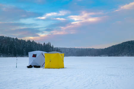 Ice fishing tent on a frozen lake at sunset. Fisherman camp on a peaceful winter evening. Banco de Imagens